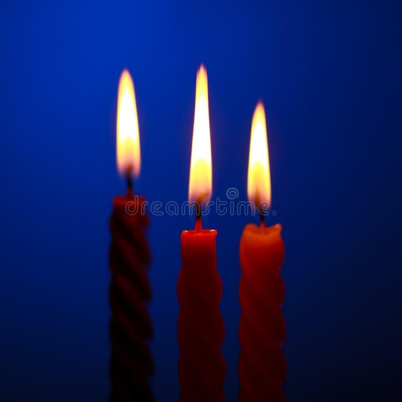 Tre candele sull'azzurro fotografia stock libera da diritti