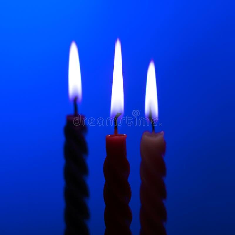 Tre candele sull'azzurro immagine stock