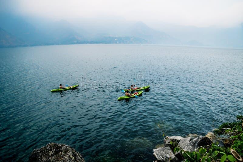 Tre canoe in lago Atitlan con le onde durante il tramonto con le montagne nebbiose, San Pedro de la Laguna, Guatemala immagine stock libera da diritti