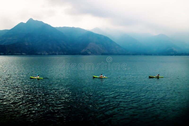 Tre canoe in una fila in lago Atitlan durante il tramonto con le montagne nebbiose, San Pedro de la Laguna, Guatemala immagine stock