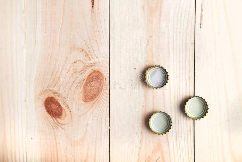 Tre cappucci da birra su un bordo di legno, immagini stock