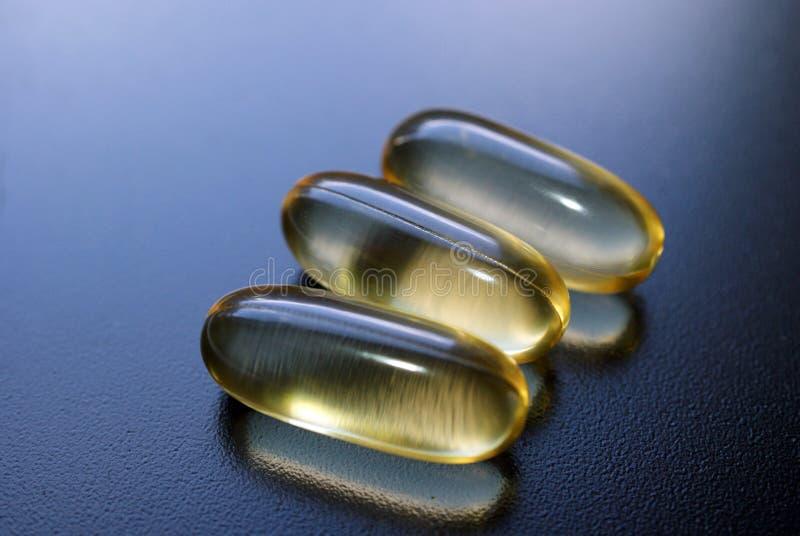 Tre capsule dell'olio di pesce immagini stock libere da diritti
