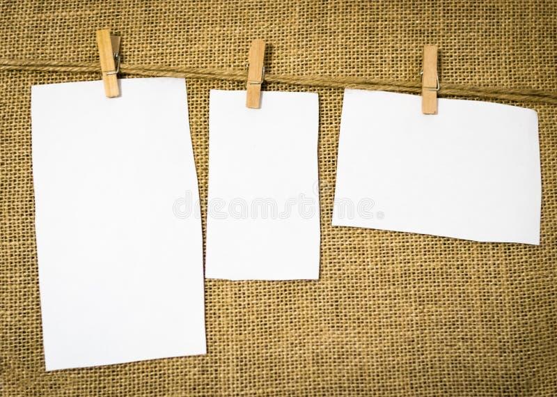 Tre carte in bianco hanno peso da un gancio d'annata rustico fotografia stock