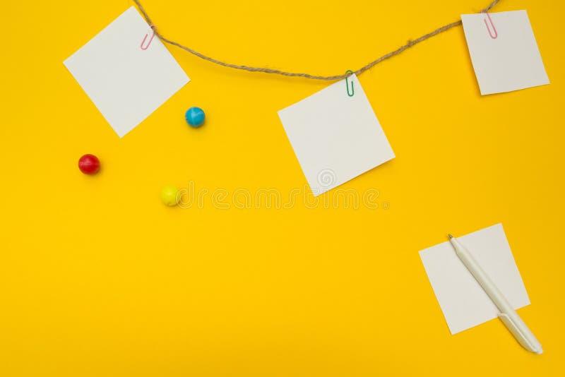Tre carte per appunti vuote allegate ad una corda su un fondo giallo Composizione piana immagini stock libere da diritti
