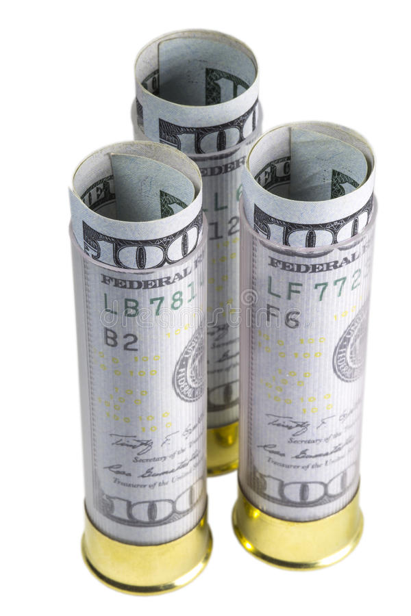 Tre 12 cartucce del fucile da caccia di calibro caricate con cento banconote in dollari Isolato su priorità bassa bianca fotografie stock