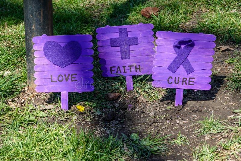 Tre case hanno fatto cartelli di viola su un prato di prato per commemorare il giorno della consapevolezza dell'autismo Dicono am fotografie stock