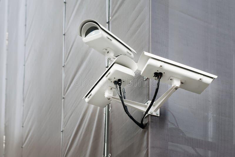 Tre CCTV-kameror på hörn av byggnad under återställande- eller förnyandedet fria Säkerhetskameror på väggen av konstruktionsbyggn arkivfoton