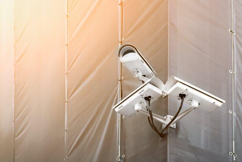 Tre CCTV-kameror p? h?rn av byggnad under ?terst?llande- eller f?rnyandedet fria S?kerhetskameror p? v?ggen av konstruktionsbyggn royaltyfria foton