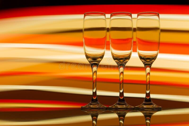 Tre champagneexponeringsglas i rad med en regnbåge av färgrik ljus målning bak dem fotografering för bildbyråer