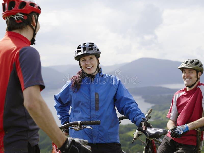 Tre ciclisti che sorridono all'aperto fotografia stock