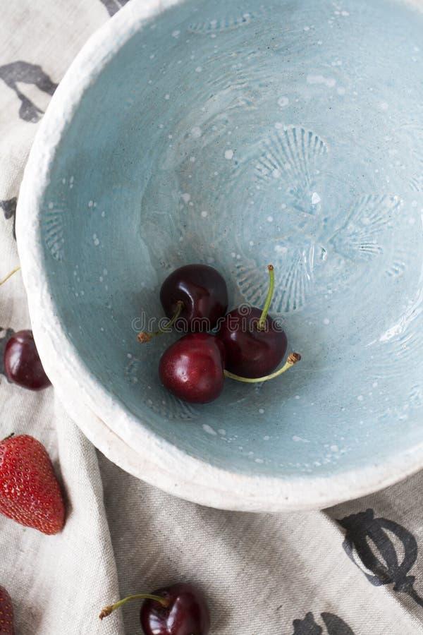 Tre ciliege rosse succose in un piatto profondo blu fotografia stock libera da diritti