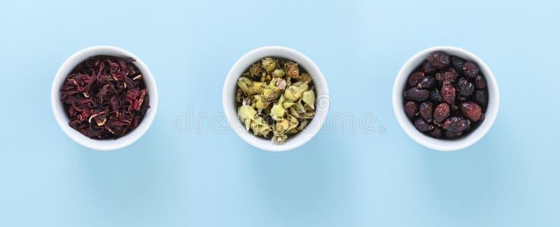 Tre ciotole bianche con gli ibischi, Ironwort e tè rosa selvaggio, su fondo blu fotografia stock