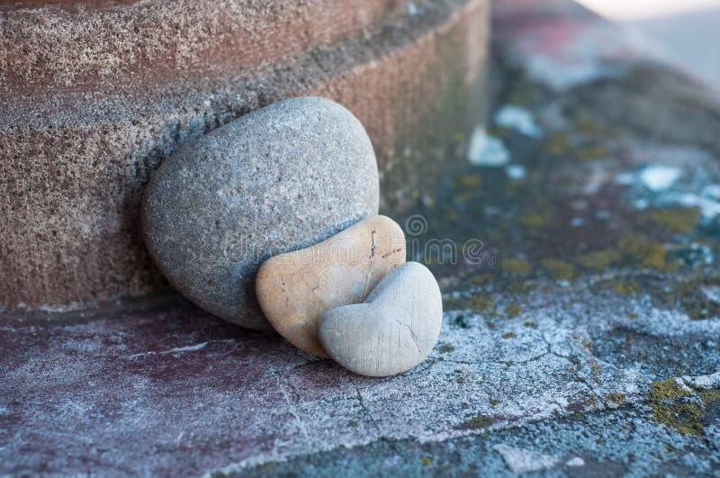 Tre ciottoli di pietra nel cuore a forma di sulla parete lapidata in all'aperto - concetto di amore fotografia stock