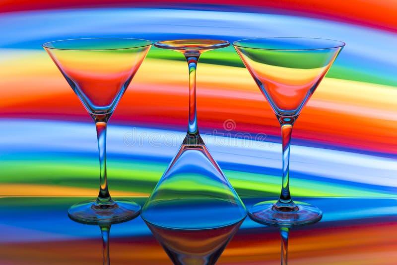 Tre cocktail/vetri di martini in una fila con un arcobaleno di colore dietro loro fotografia stock libera da diritti