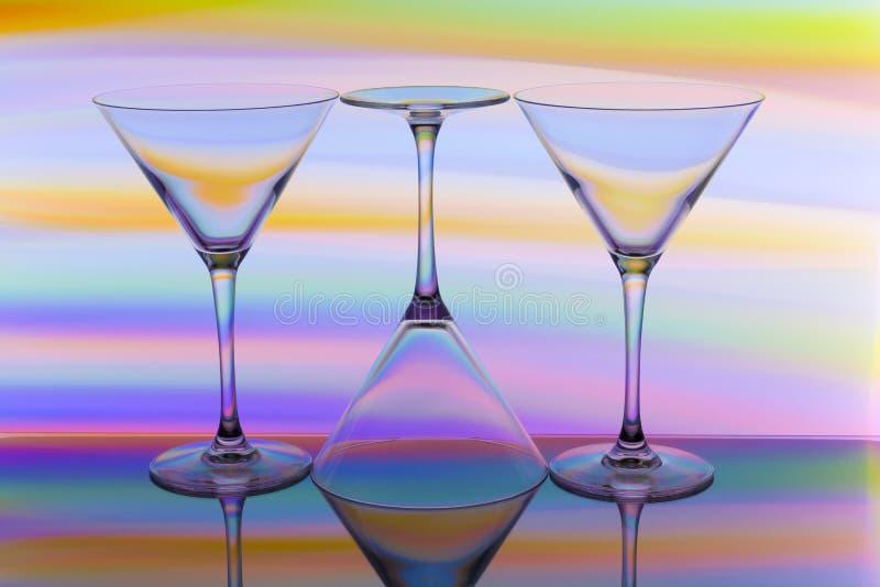 Tre coctail/martini exponeringsglas i rad med en regnbåge av färg bak dem arkivbilder