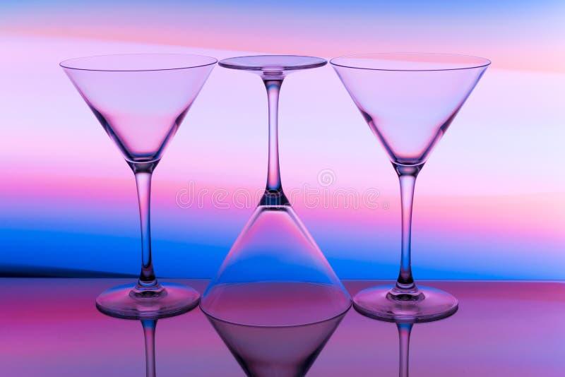 Tre coctail/martini exponeringsglas i rad med en regnbåge av färg bak dem royaltyfri bild