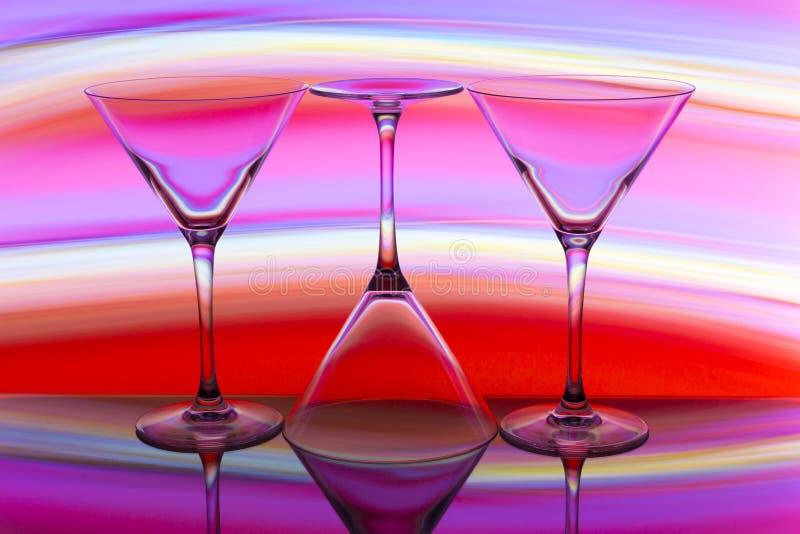 Tre coctail/martini exponeringsglas i rad med en regnbåge av färg bak dem royaltyfri fotografi
