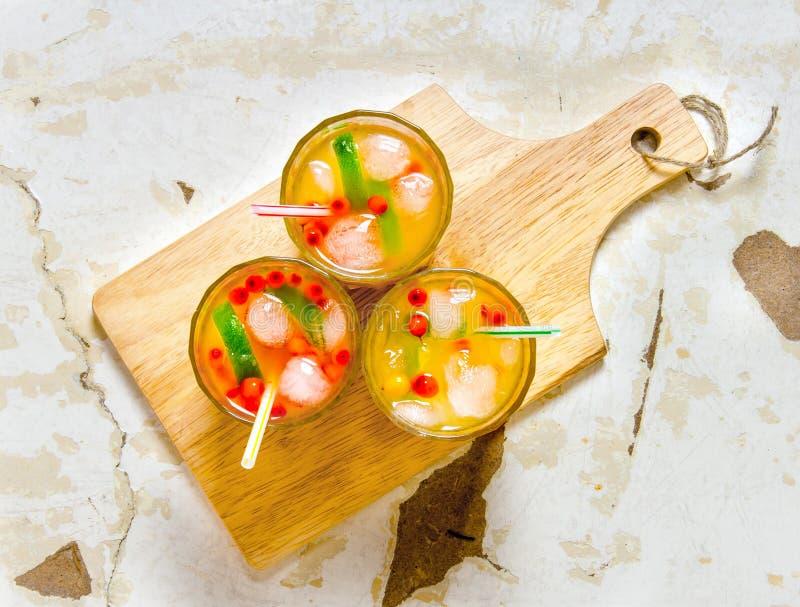 Tre coctailar från hav-buckthorn bär, is och limefrukt på den gamla tabellen fotografering för bildbyråer