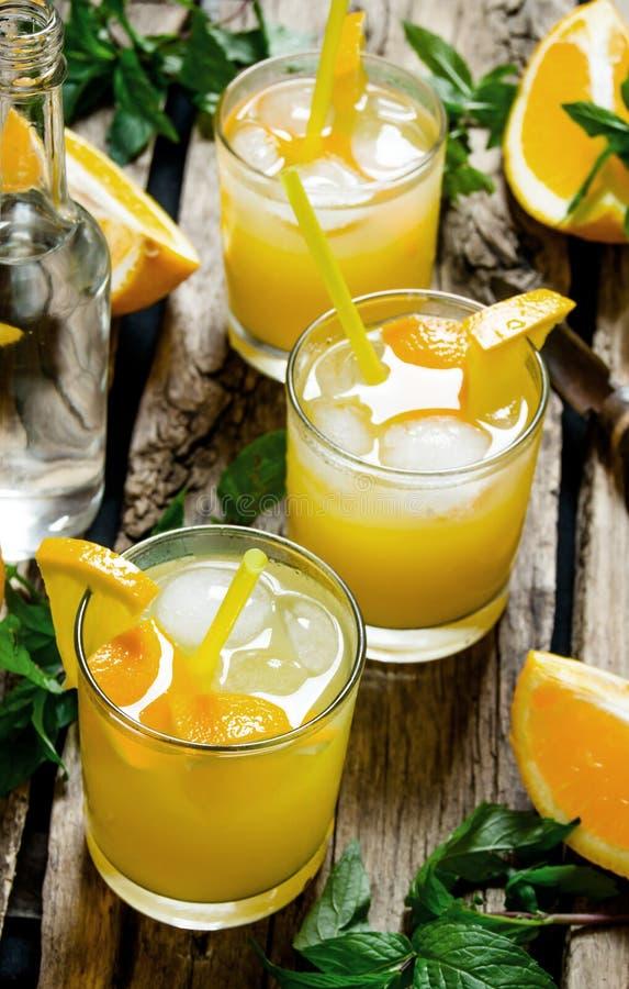 Tre coctailar från nya apelsiner med is- och mintkaramellsidor på träbakgrund arkivfoto