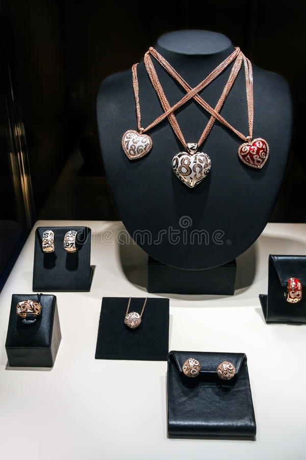 Tre collane fatte di bianco e di oro rosa su un supporto Pendenti in forma di cuore con i diamanti Insieme di gioielli di lusso c fotografie stock