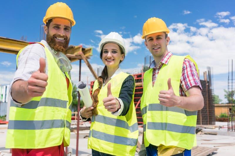 Tre colleghi in una costruzione team mostrando i pollici su fotografia stock