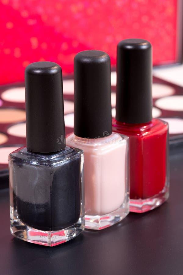 Tre colori differenti dello smalto e un fondo di comporre - rosso, persona neutrale ed il nero fotografie stock