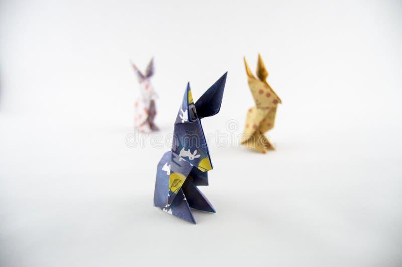 Tre conigli di origami su fondo bianco fotografia stock