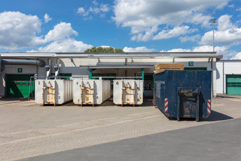 Tre contenitori bianchi dell'immondizia stanno stando su un sito della fabbrica e ci sono altri contenitori dell'immondizia accan immagini stock libere da diritti