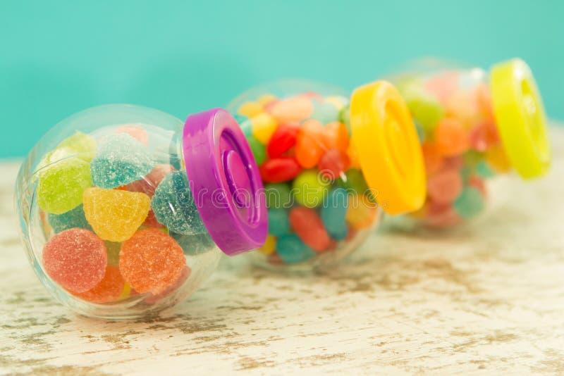 Tre contenitori di vetro in pieno dei jellybeans con fondo blu immagine stock libera da diritti