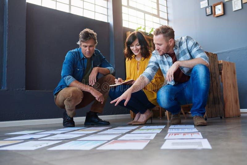 Tre coworkers som diskuterar skrivbordsarbete som läggas ut på ett kontorsgolv arkivbild