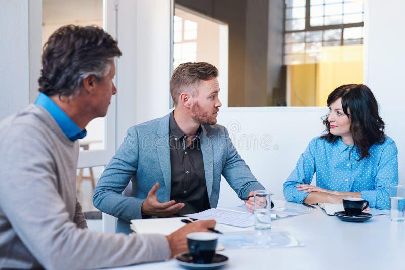 Tre coworkers som har ett strategimöte i ett modernt kontor royaltyfri bild