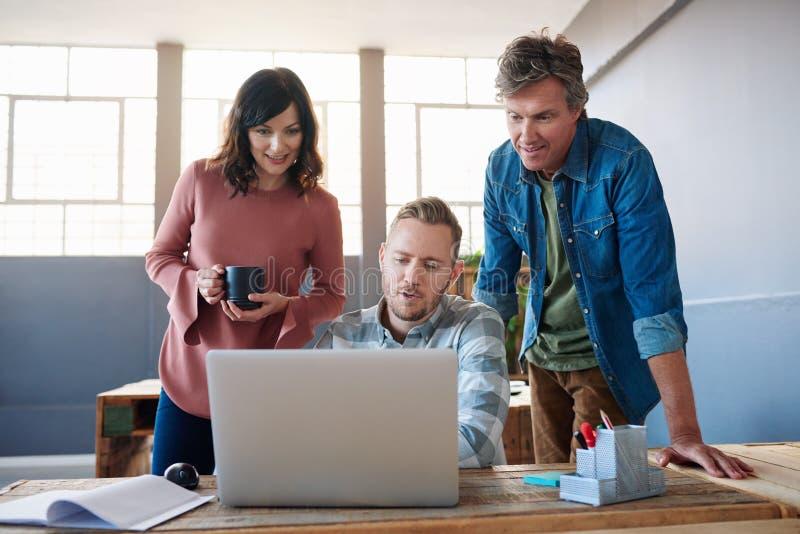 Tre coworkers som tillsammans använder en bärbar dator i ett modernt kontor royaltyfria bilder