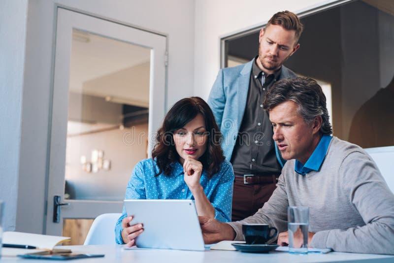 Tre coworkers som tillsammans använder en digital minnestavla i ett kontor arkivfoton