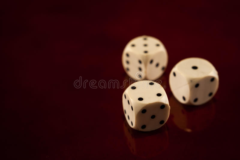 Tre cubi dei dadi su buio che riflette fortuna di legno dei giochi del fondo fotografie stock libere da diritti