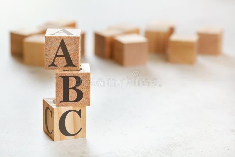 Tre cubi di legno con lettere ABC significa sempre chiudersi, sulla tavola bianca, più in background, spazio per il testo in giù fotografia stock libera da diritti
