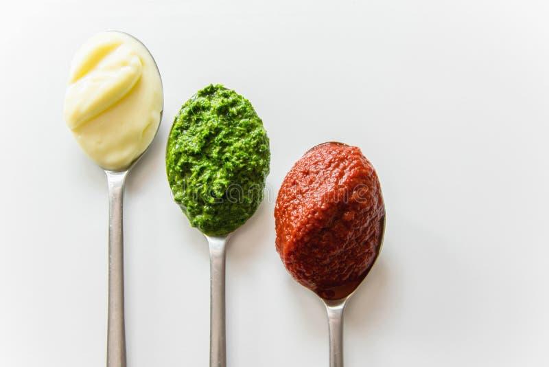 Tre cucchiai con differenti condimenti - maionese, salsa al pomodoro e pesto fotografie stock