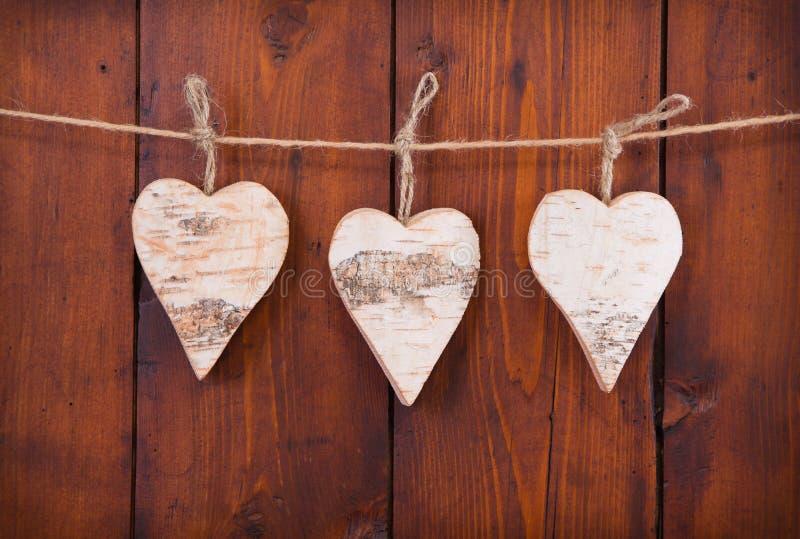 Tre cuori di legno d'attaccatura. immagine stock libera da diritti
