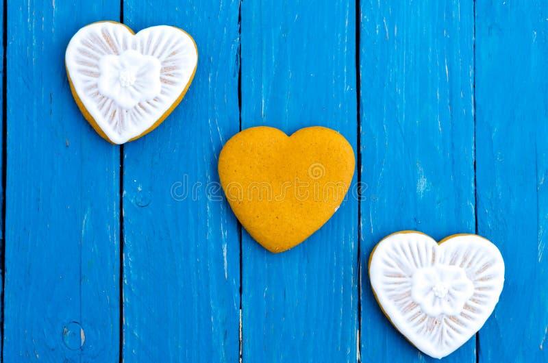 Tre cuori diagonalmente gingerbread Fondo di legno del turchese Disposizione piana fotografia stock