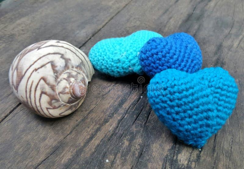 Tre cuori e conchiglie blu una sulla sedia di spiaggia di legno