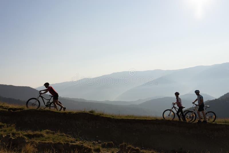 Tre cyklister på en bergslinga royaltyfri bild