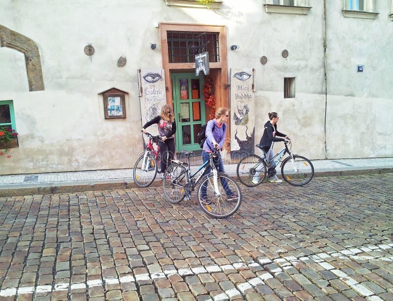 Tre cyklistflickor som lämnar det Maly Buddha kafét arkivbilder