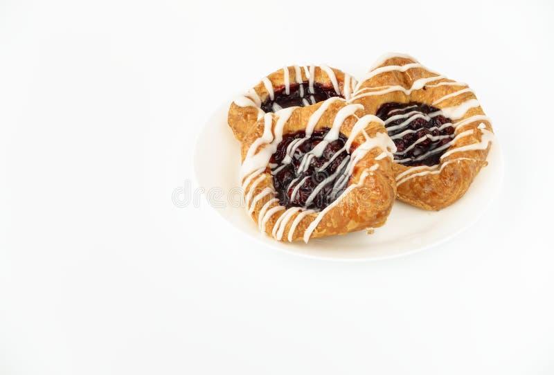 Tre danska Cherry Pastries på den vita plattan royaltyfria bilder
