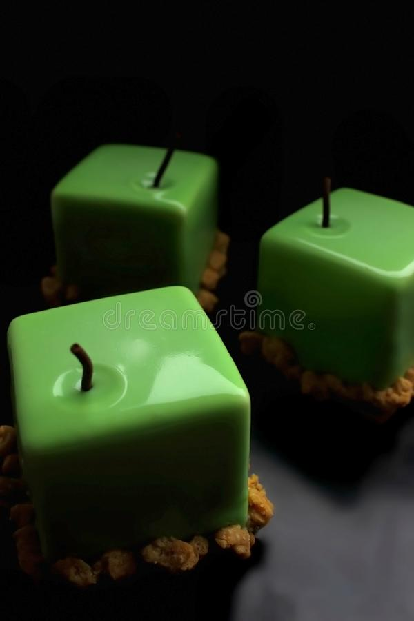 Tre dessert lustrati brillanti del cubo della mela verde su fondo nero fotografia stock libera da diritti