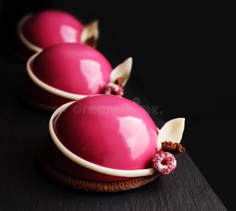 Tre dessert rosa girly della mousse del lampone con le decorazioni della cioccolata bianca e le bacche fresche fotografia stock libera da diritti