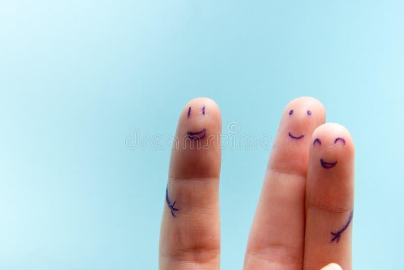 Tre dita sorridenti che sono molto felici di essere amici Concetto di lavoro di squadra di amicizia su fondo blu con lo spazio de fotografia stock libera da diritti