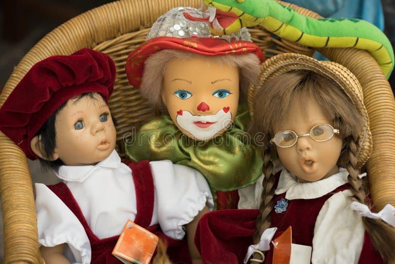 Tre dockor i en stol royaltyfria bilder