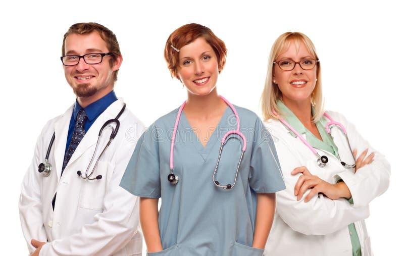 Tre doktorer och sjuksköterskor på en vit bakgrund royaltyfri fotografi