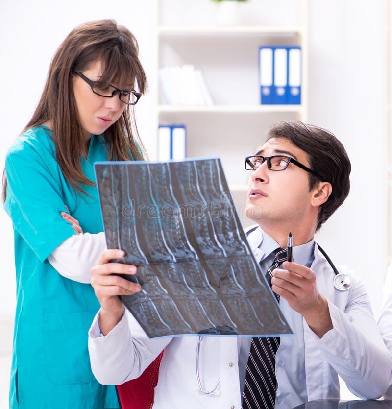 Tre doktorer som diskuterar bildl?sningsresultat av r?ntgenstr?lebilden royaltyfri fotografi