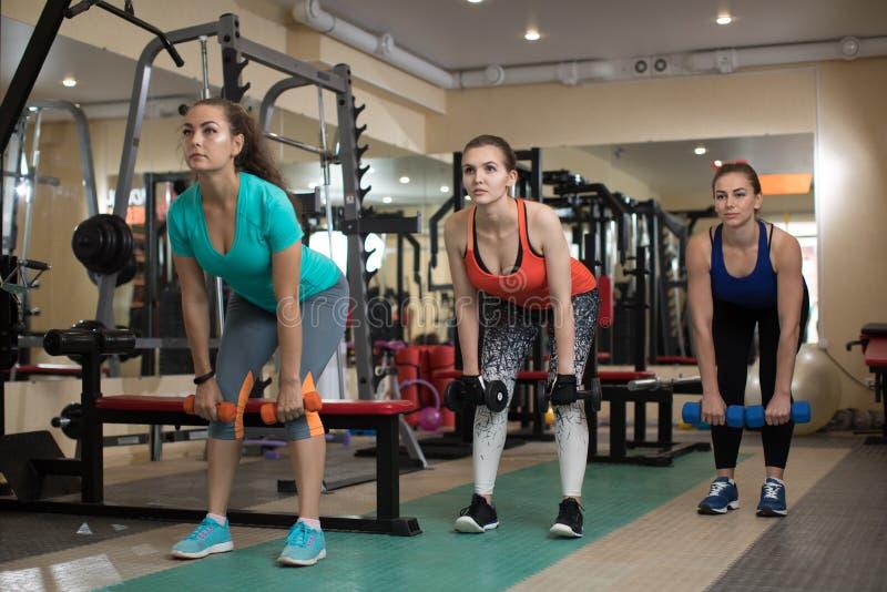 Tre donne attive di giovane forma fisica che fanno gli esercizi con i kettlebells in palestra fotografia stock libera da diritti