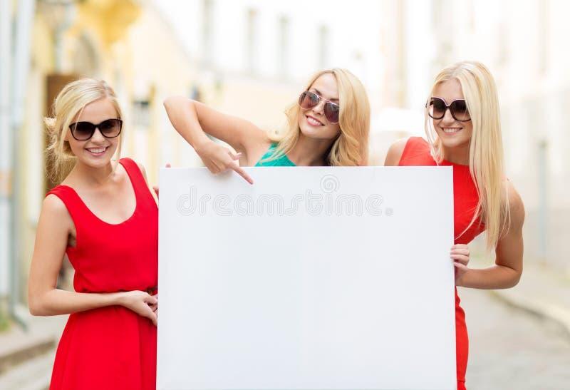 Tre donne bionde felici con il bordo bianco in bianco immagine stock libera da diritti